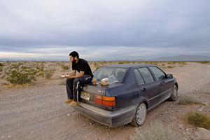 Photo of me sitting on my car eating a peanut butter sandwich.